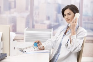 Female doctor sitting at desk in office talking on phone.